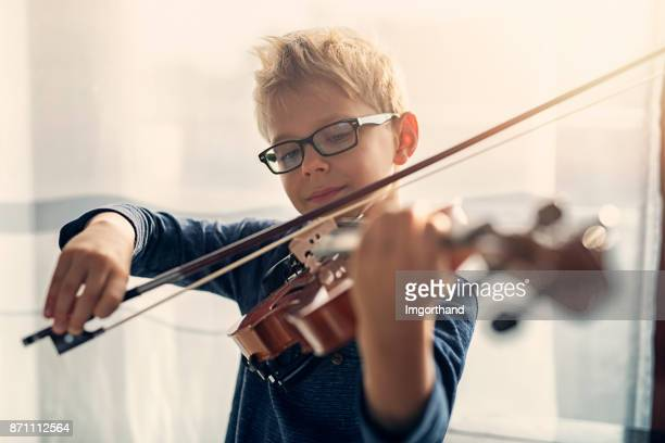 Little boy practicing violin