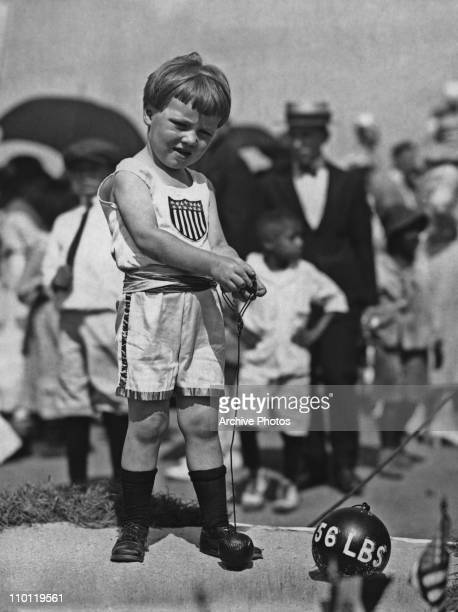 A little boy practising hammer throwing with a hammer made from a baseball USA circa 1925