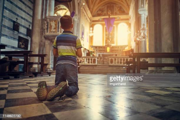 little boy praying at little church in little italian town during the holy week - lent stock pictures, royalty-free photos & images