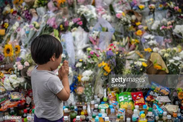 Little boy prays next to flowers laid at the scene of a knife attack on a group of schoolchildren, on May 29, 2019 in Kawasaki, Japan. An 11-year old...