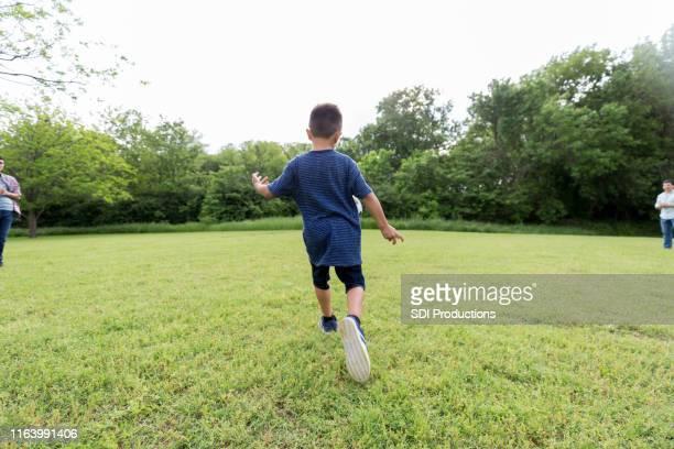 el niño se prepara para patear pelota - lanzar la pelota fotografías e imágenes de stock