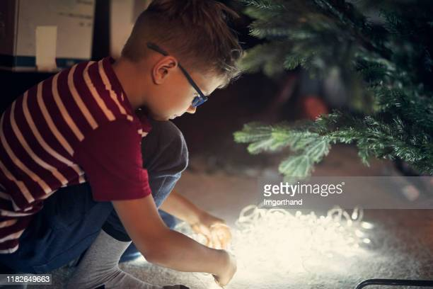 little boy preparing christmas lights on christmas tree - plugging in stock pictures, royalty-free photos & images