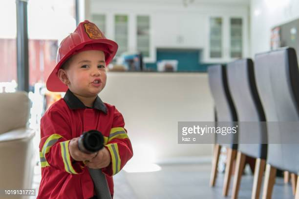little boy pretending to be a fireman - fire natural phenomenon stock pictures, royalty-free photos & images