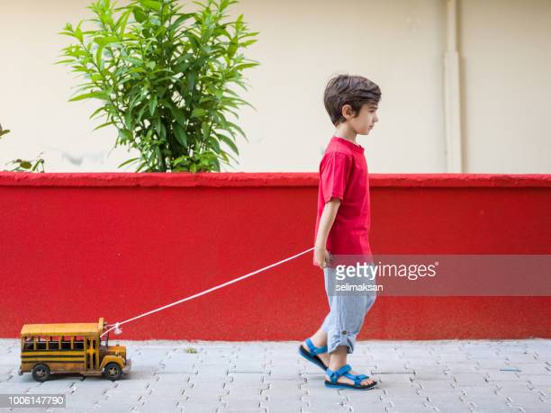 Little Boy Pulling Toy School Bus In Outdoor