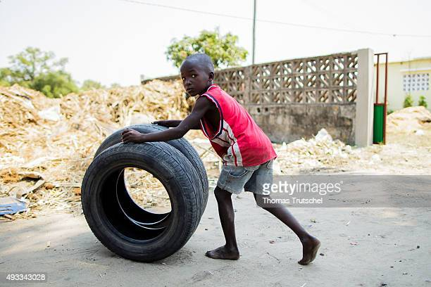 A little boy pushes old car tire over a road on September 28 2015 in Beira Mozambique