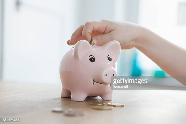 Little boy putting coin into piggy bank, close-up