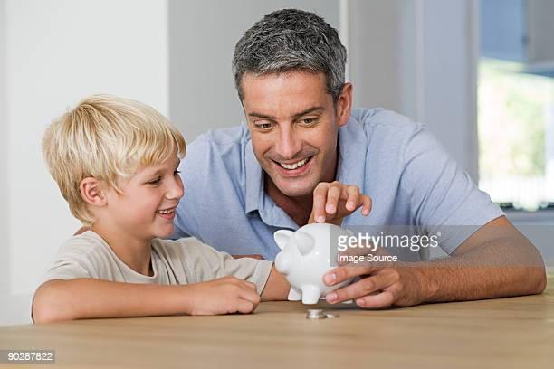 Kleine Junge setzen Münzen im Sparschwein mit seinem Vater