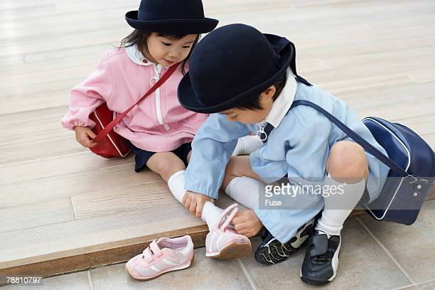 Little Boy Putting Helping His Sister with Her Shoes