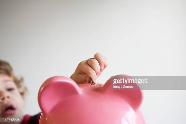 Little boy putting money in piggy bank