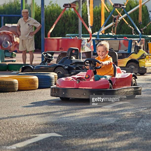 Little boy racing Go-cart in an amusement park outdoors.
