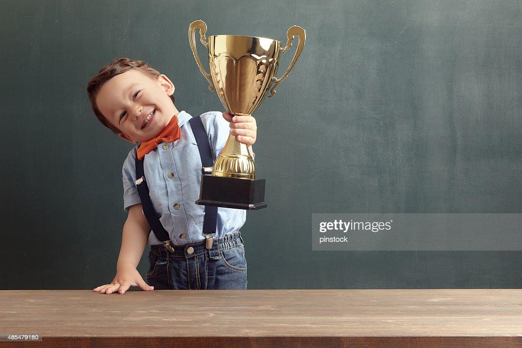 Little boy raising a golden trophy : Stock Photo