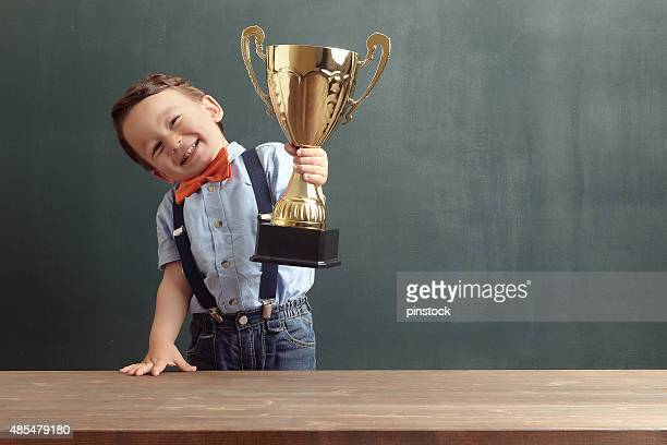 little boy raising a golden trophy - award stock pictures, royalty-free photos & images