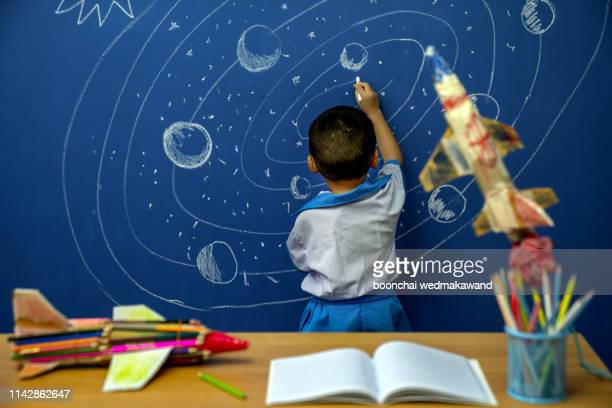 little boy reaching for rocket in drawn space - 天文学 ストックフォトと画像