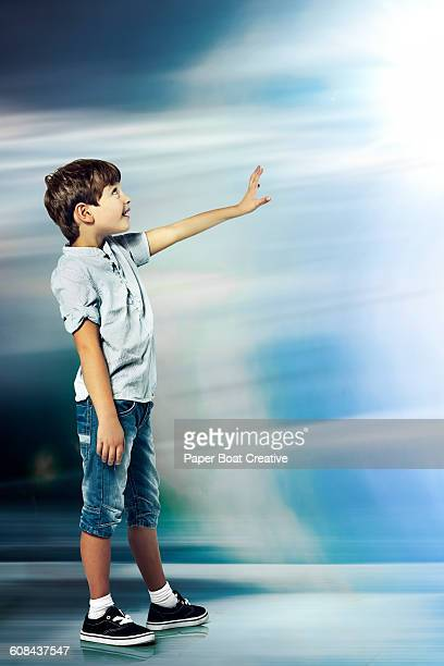 little boy reaching out to a space with light - reaching stock pictures, royalty-free photos & images