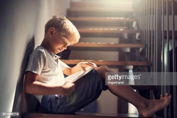 jongetje lezen van een boek op de trap - lezen stockfoto's en -beelden