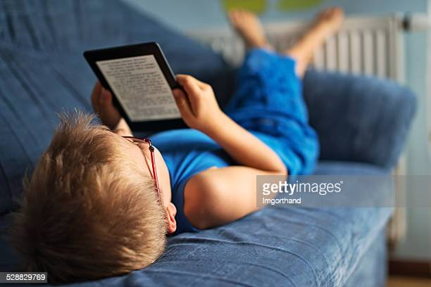 Little boy reading an ebook on couch