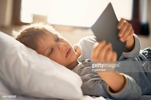 Little boy reading an ebook on sunny morning