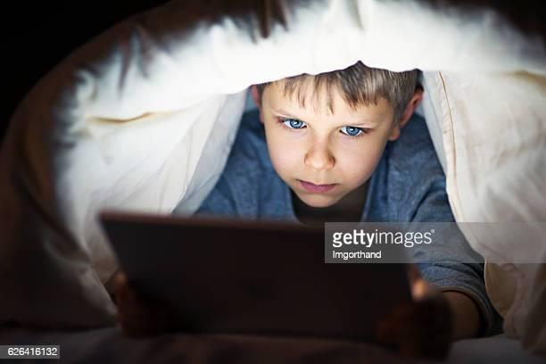 Little boy reading book on digital tablet at night