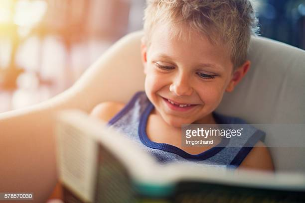 Little boy reading funny book
