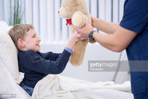 little boy recieving a teddy bear - paraplegic stock photos and pictures