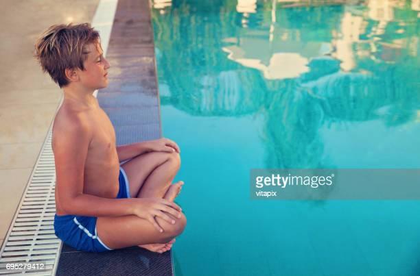 jongetje ontspannen bij het zwembad - lotuspositie stockfoto's en -beelden