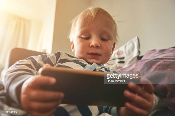 Little boy relaxing on sofa using mobile phone