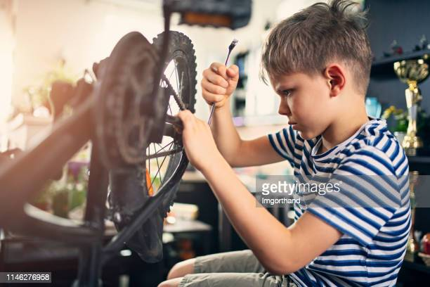 little boy repairing a bicycle at home - adjusting stock pictures, royalty-free photos & images