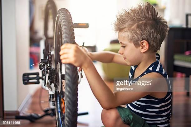 Kleiner Junge auf einem Fahrrad zu Hause reparieren