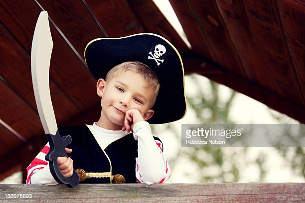 Little boy resting head on hand dressed as pirate