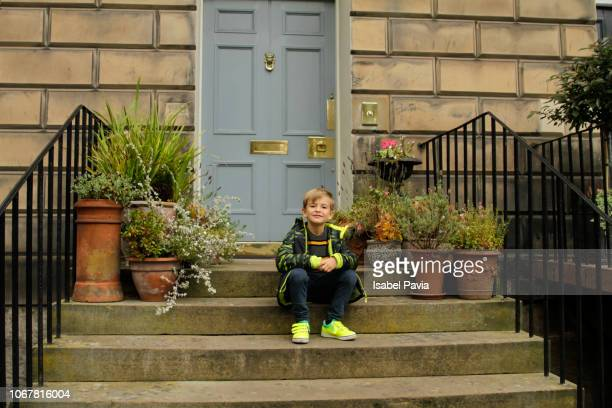 little boy resting in front of house - in front of stock pictures, royalty-free photos & images