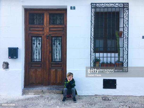 Little boy resting in front of house