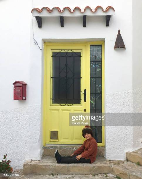 Little boy resting in front of yellow house