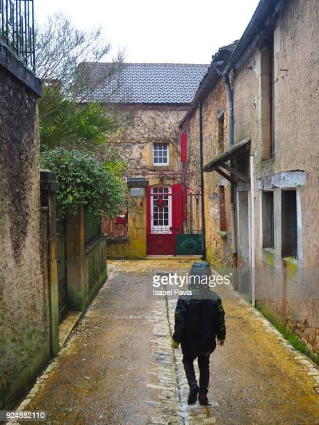 Little boy returning home under the rain