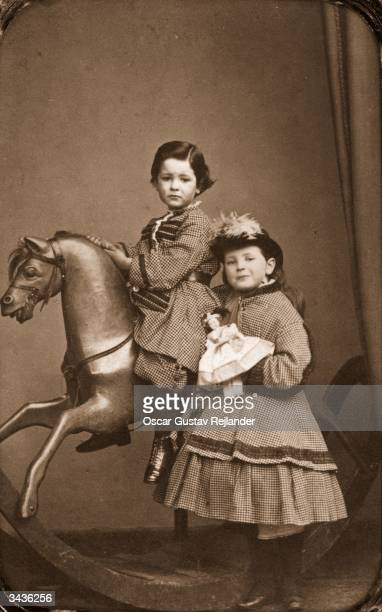 A little boy rides a rocking horse while his sister stands by his side holding her doll