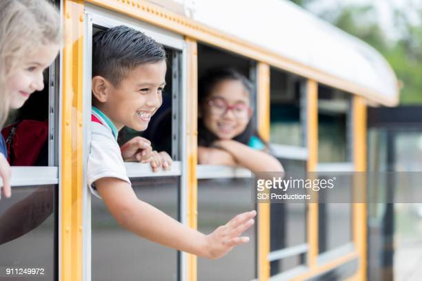 Little boy rides a school bus with his friends