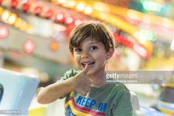 little boy rides at the fairground attractions in amusement park - 遊園地の乗り物 ストックフォトと画像