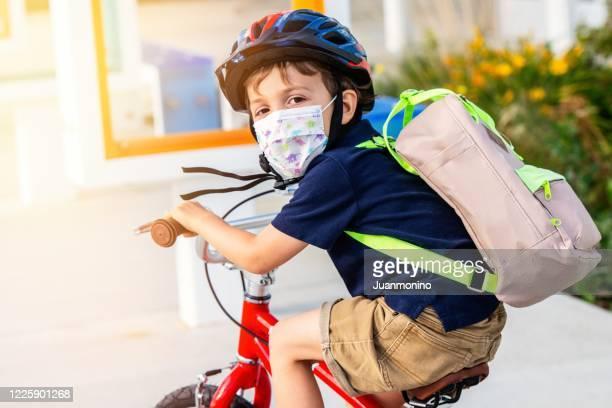 little boy riding a bicycle wearing a protective mask - regresso às aulas imagens e fotografias de stock