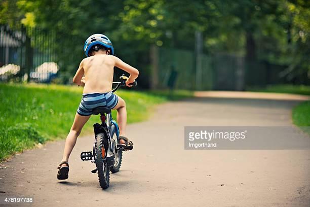Petit garçon d'équitation un vélo sur une chaude journée