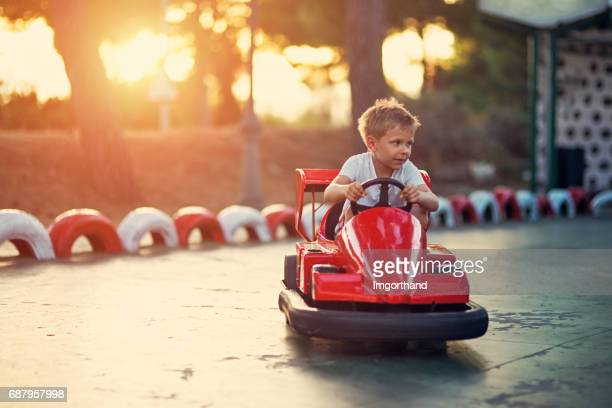 Little boy riding a funfair bumper car