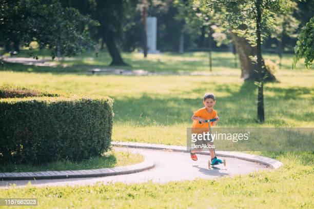 bambino in sella a uno scooter push - solo bambini foto e immagini stock