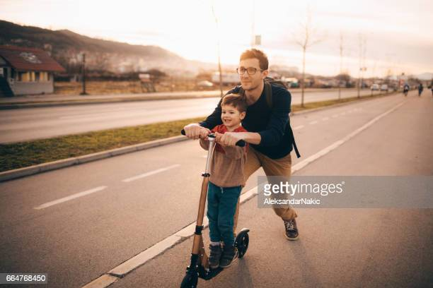 Petit garçon trottinette pousser avec son papa
