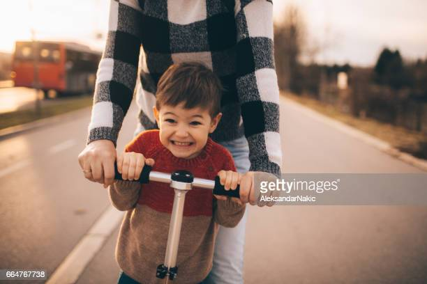 Little boy riding a push scooter with his mom