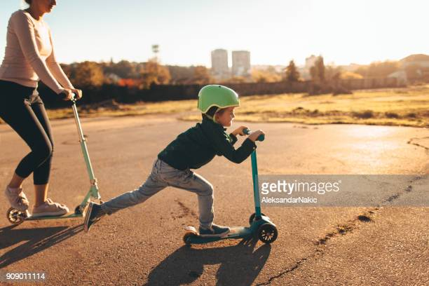 little boy riding a push scooter with his mom - spring racing stock photos and pictures