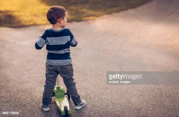 小男孩騎踏板車 - 跟拍鏡頭 個照片及圖片檔