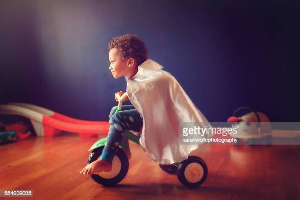little boy riding a tricycle in a super hero cape - tricycle stock pictures, royalty-free photos & images