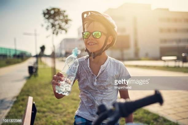kleine jongen rijden fiets- en drinkwater - warmte stockfoto's en -beelden