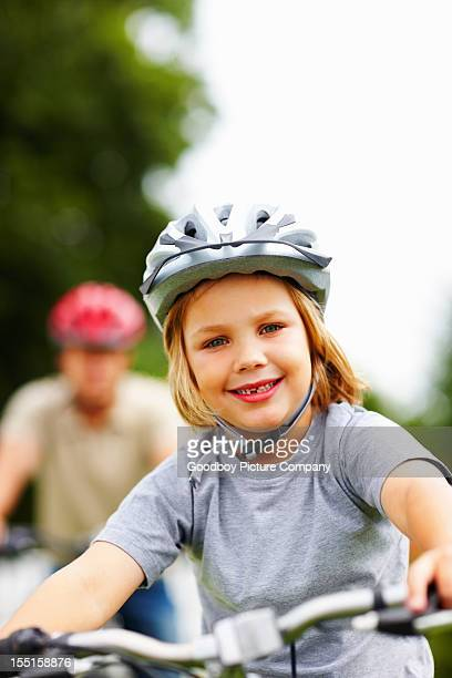 Little boy riding bicycle with his blur father in background