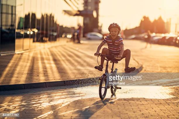 Little boy riding his bike through a puddle