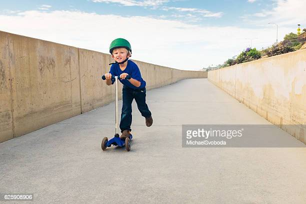 Little Boy Riding His Scooter Down A Bike Path