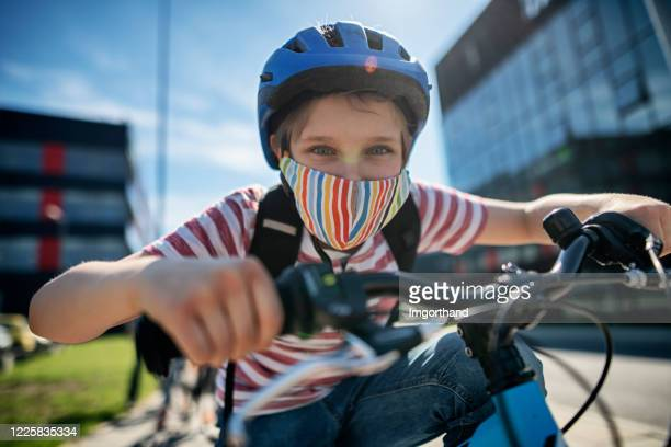 little boy riding to school during covid-19 pandemic - helmet stock pictures, royalty-free photos & images